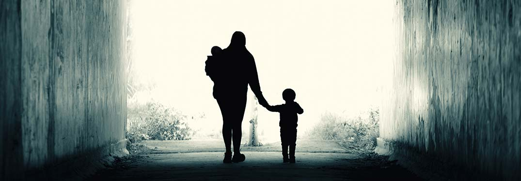 Image of a woman and her children walking into a tunnel at the park