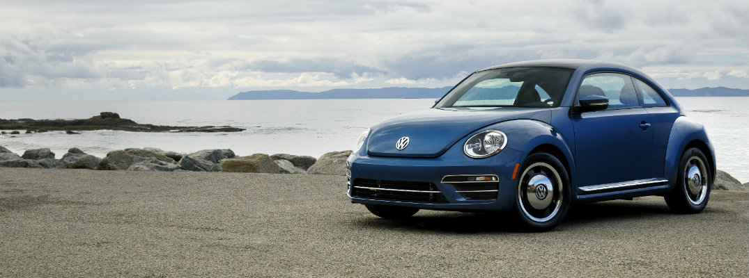 Blue Volkswagen Beetle near the ocean