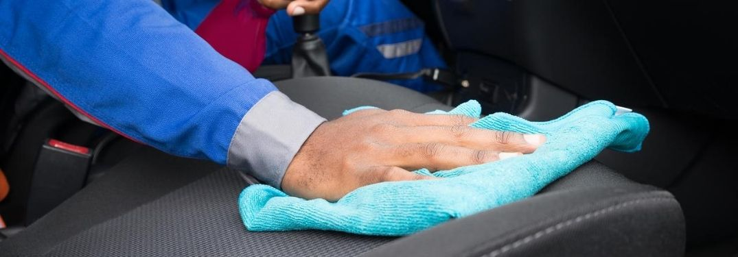 person wiping down car seat with blue cloth