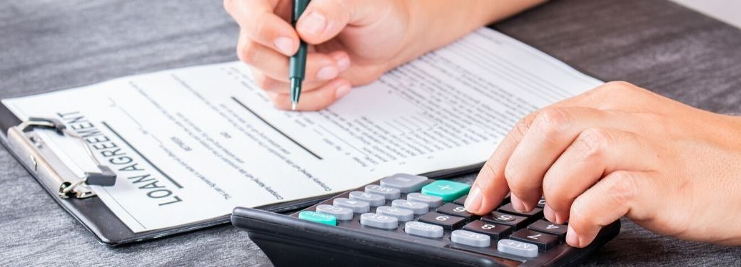 person using calculator and pen to sign paperwork