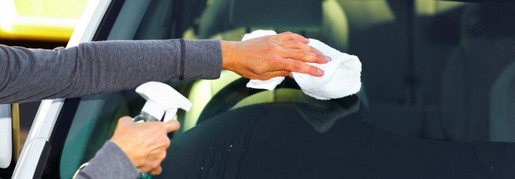 person wiping down the car windshield with a white cloth