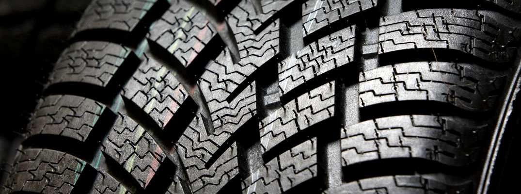 Where on a tire do you insert the penny to test its tread?