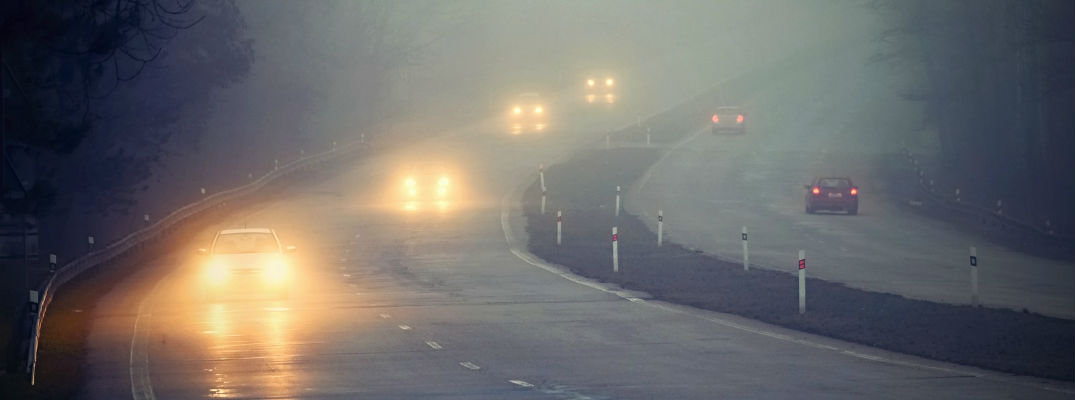 A photo of cars driving through fog with their headlights on