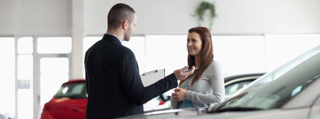 A stock photo of a young woman being helped by a car dealership's representative