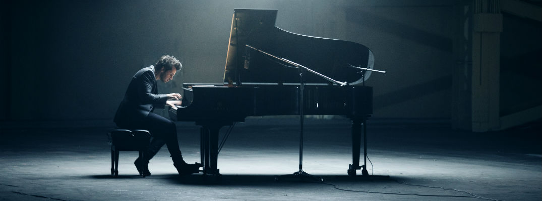 A photo of a musician playing the piano for a new Mitsubishi commercial for the 2018 Eclipse Cross.