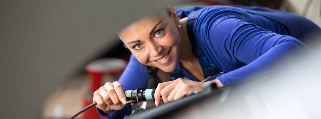 A stock photo of a service technician working on a vehicle.