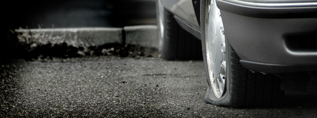 A stock photo of a car with a flat tire in a parking lot.