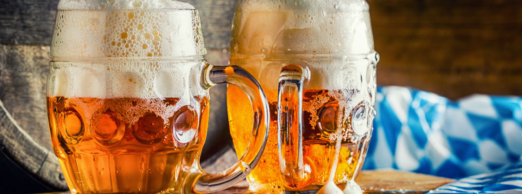 A stock photo of two full beer steins and an Oktoberfest tablecloth.