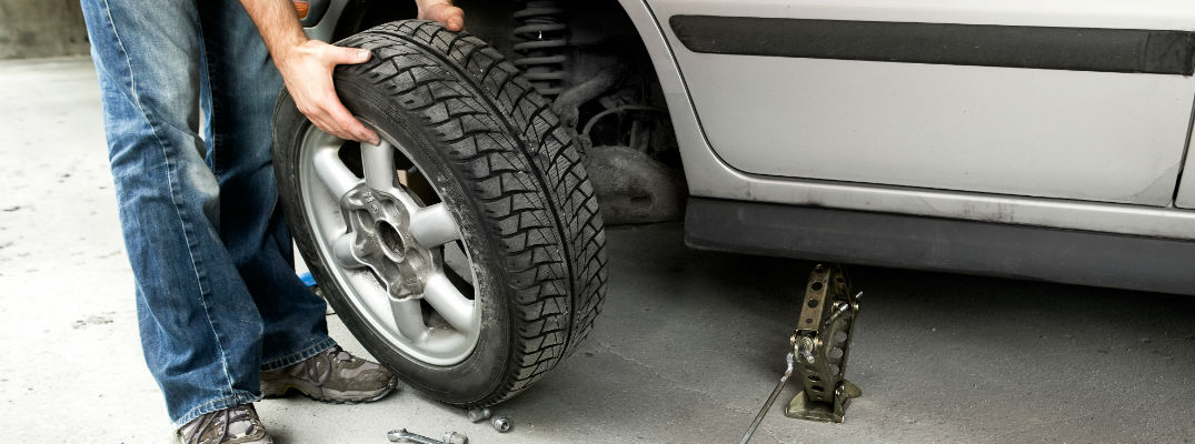 A stock photo of a person changing a tire.
