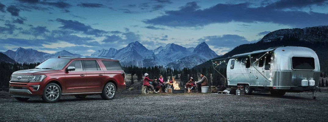 A family camping around the 2018 Ford Expedition at dusk