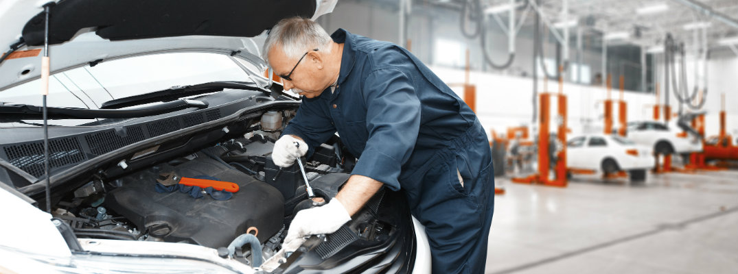 Mechanic working under the hood of a car