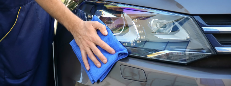 Man polishing shiny car headlight