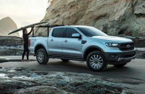 2019 Ford Ranger at the beach with a person putting a surfboard in the truck bed