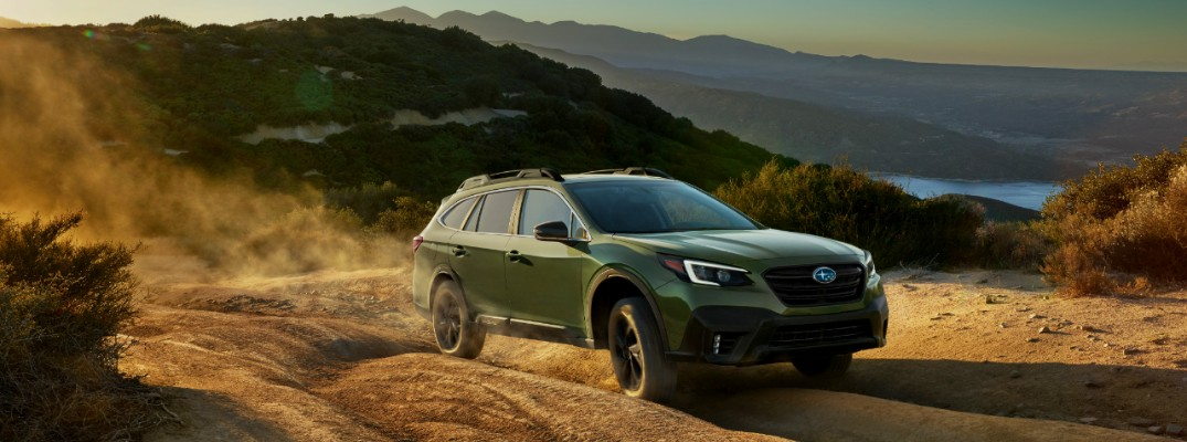 2020 Subaru Outback driving through a dusty trail between mountains