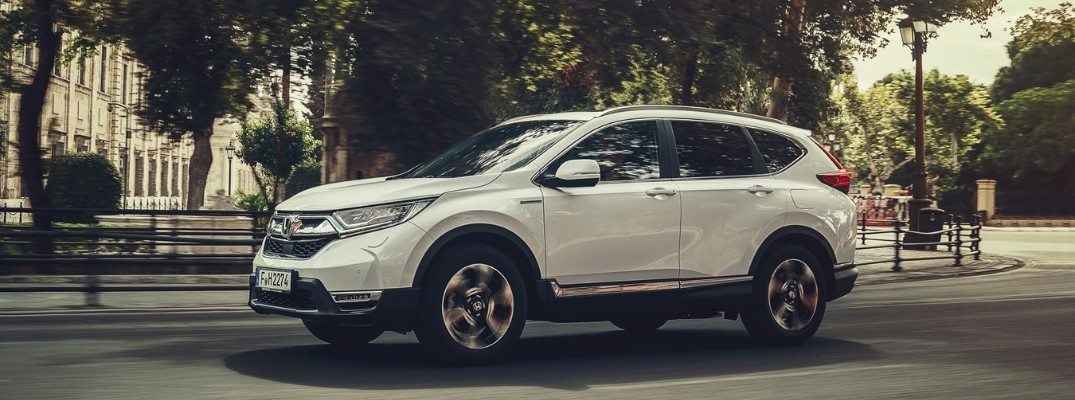 2019 Honda CR-V Hybrid driving past a city park