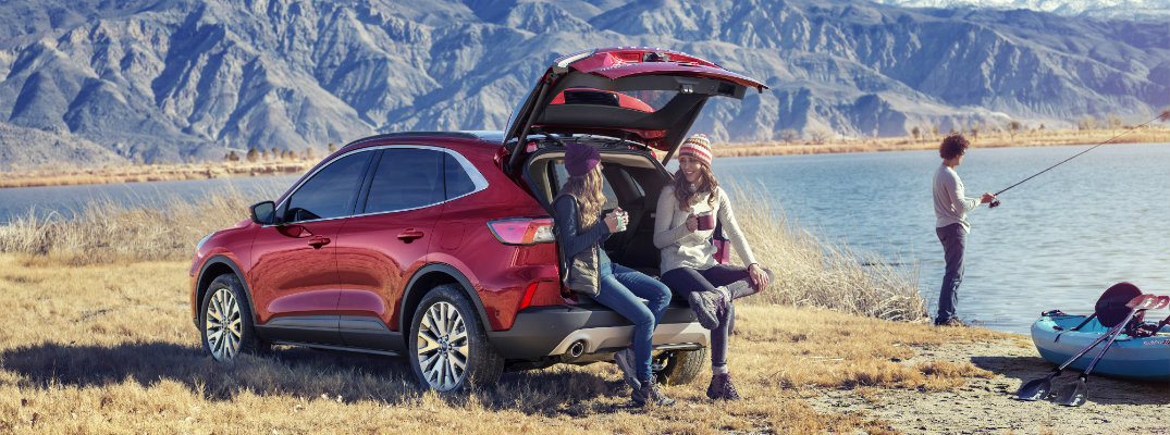 Two woman drinking coffee in the open hatch of the 2020 Ford Escape while a man fishes in a pond nearby