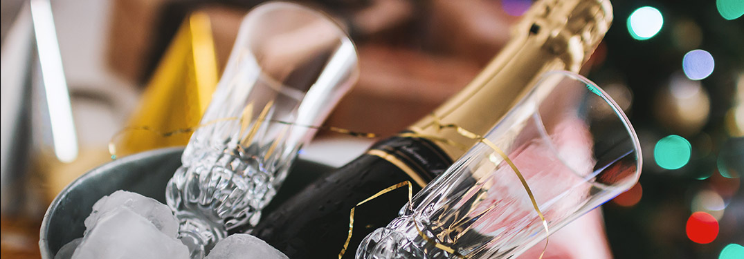 A champagne bottle on ice with glasses