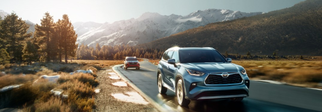 Two 2020 Toyota Highlander models driving down a rural road