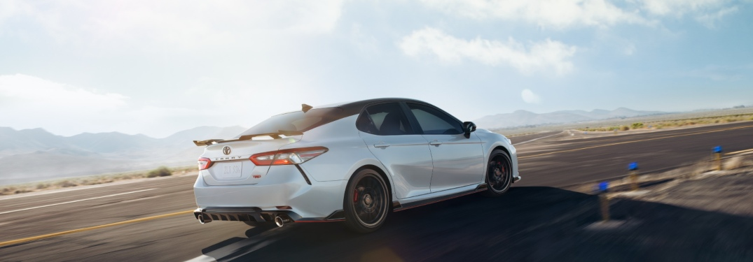 2020 Toyota Camry driving down a sunny highway road