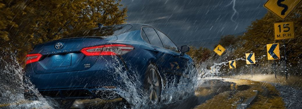 A 2020 Toyota Camry driving down a road during a storm