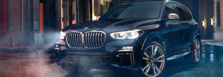 2020 BMW X5 driving down a misty street