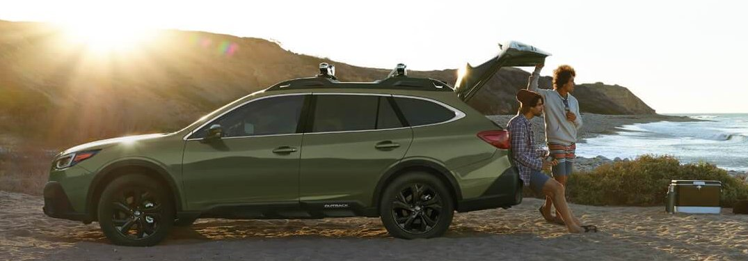 Two people leaning on a 2020 Subaru Outback parked on a beach