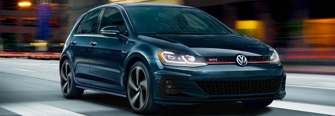 2020 Volkswagen Golf GTI driving down a city street at night