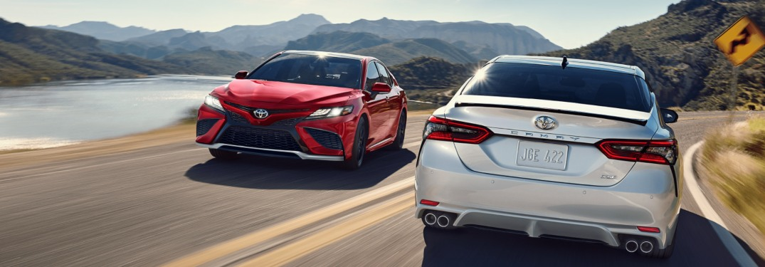 Two 2021 Toyota Camry models passing by one another on a road