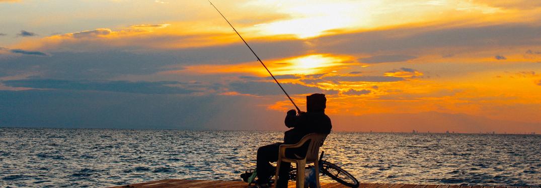 A man at a pier fishing at dawn