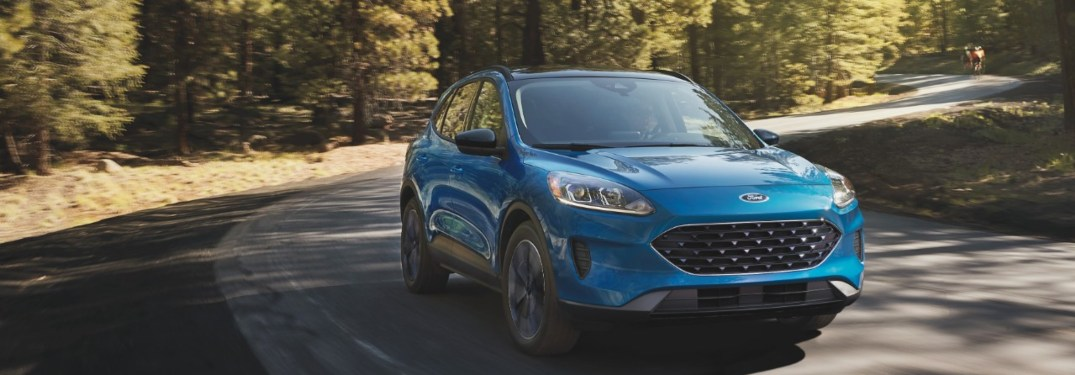 2021 Ford Escape driving down a road at sunset