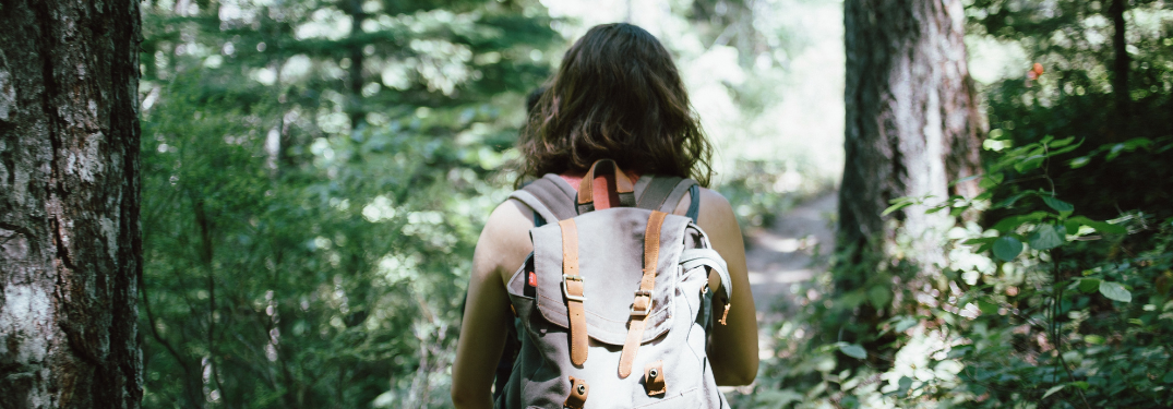 A woman hiking through woods with a backpack
