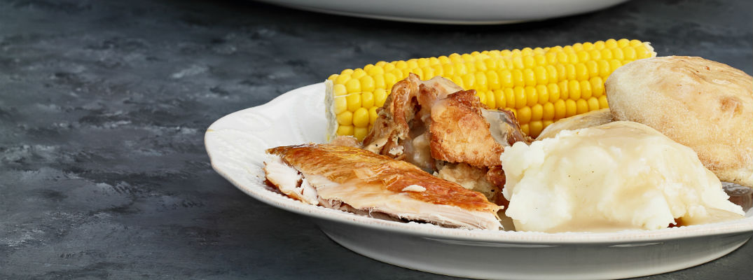 A stock photo close up of a plate covered with turkey, potatoes and an ear of corn