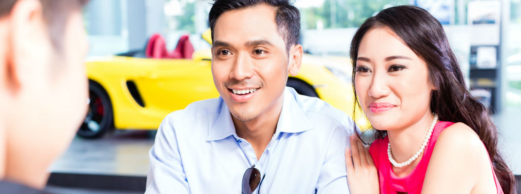 A stock photo of a young couple getting answers at a dealership