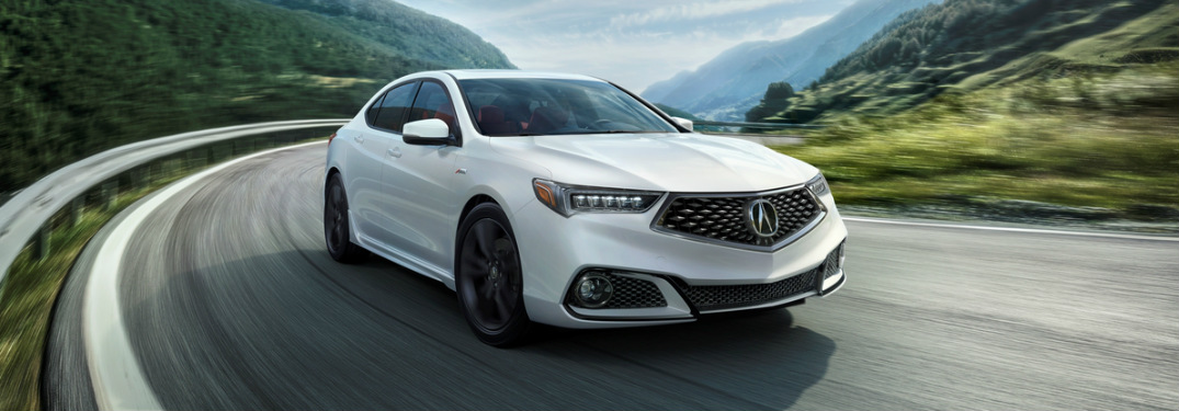 2019 Acura TLX in white driving around a corner in the mountains