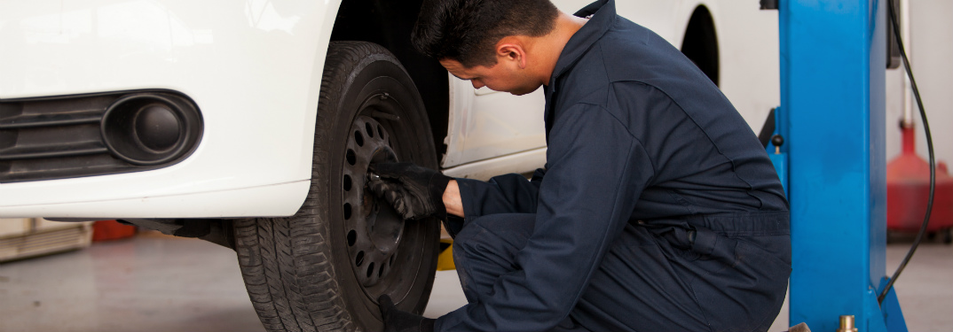 mechanic working on the tire of a raised car