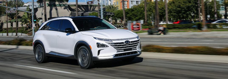 white Hyundai NEXO driving down city street