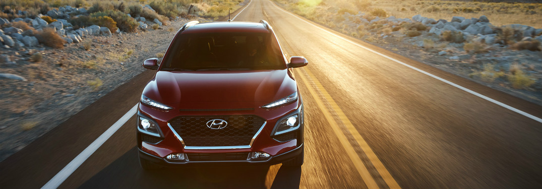 Front view of a 2018 Hyundai Kona driving past a sunset