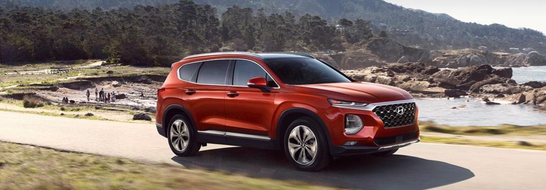 Red 2019 Hyundai Santa Fe driving along trail