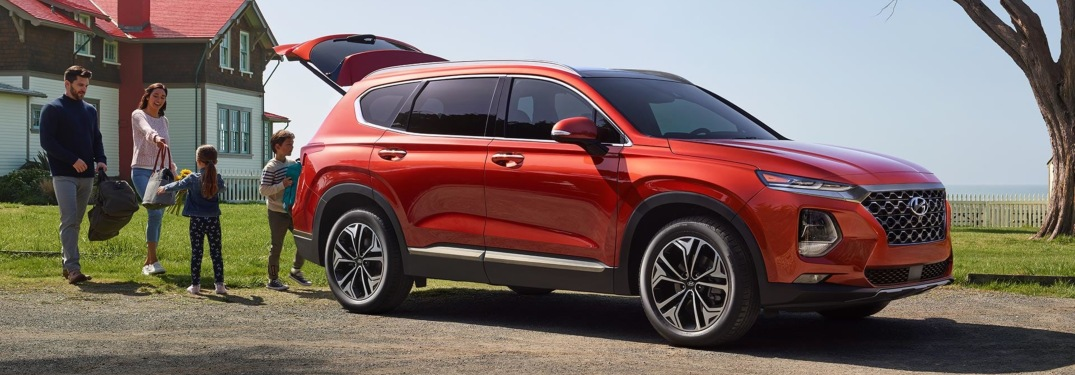 Family walking beside red 2019 Hyundai Santa Fe
