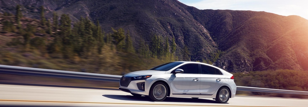 Side view of a silver 2019 Hyundai Ioniq Hybrid driving besides mountains
