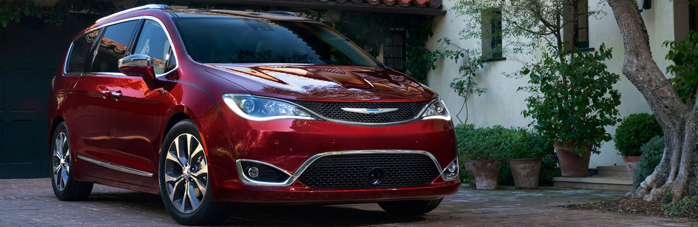 Red 2018 Chrysler Pacifica minivan parked in the woods