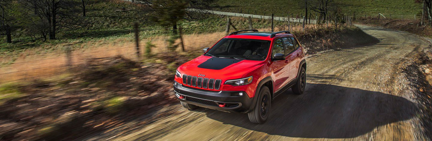 red 2019 Red Jeep Cherokee driving on a dirt road