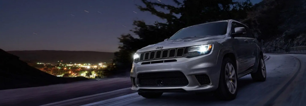 2018 Jeep Grand Cherokee driving down a highway at night