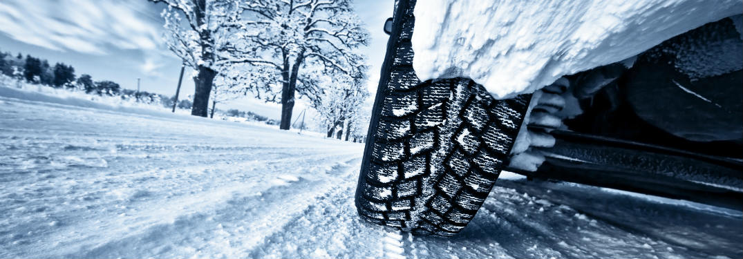 Close-up of a vehicle's winter tire on a snowy road