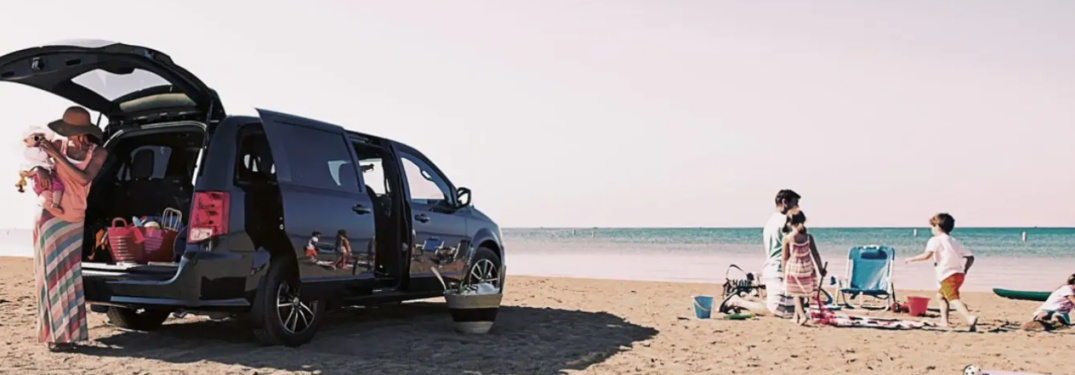 2019 Dodge Grand Caravan parked on a beach with a woman getting luggage out of its cargo area