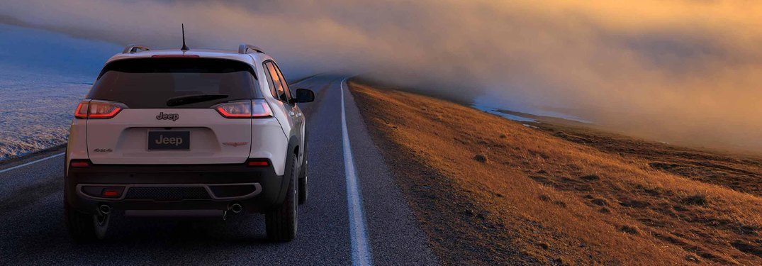 2019 Jeep Grand Cherokee driving down a country road at sunset