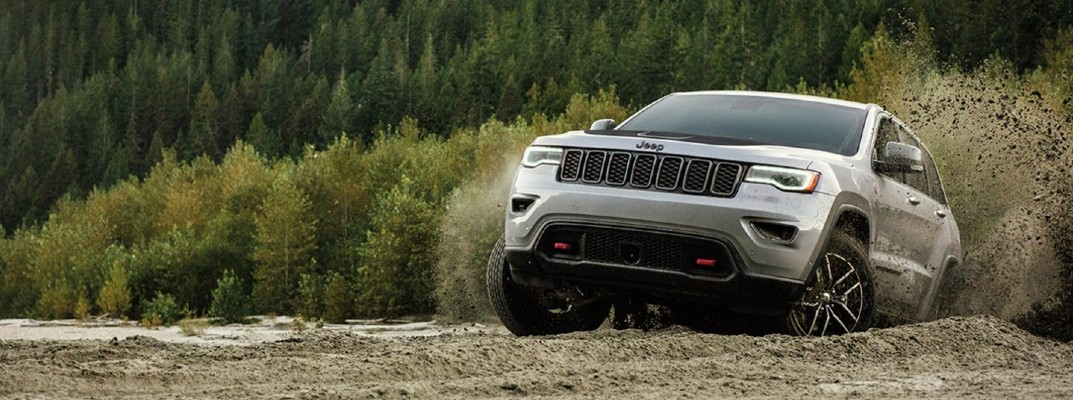 2020 Jeep Grand Cherokee driving through dirt with forest background throwing clods into the air