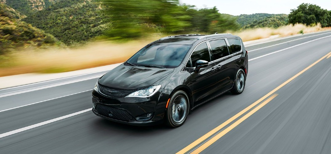 2020 Chrysler Pacifica black paint driving down highway showing front and driver side reflecting clouds