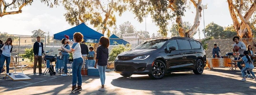 2020 Chrysler Pacifica black parked in parking lot of park with tents and people