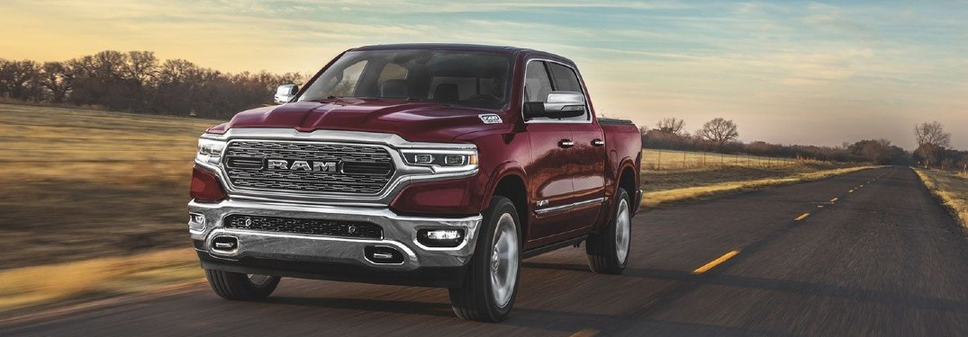 2020 Ram 1500 dark red paint driving on country road toward shot at sunset showing front bumper and driver side doors